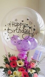 Clear Balloon stuffed with balloons and happy birthday print with basket of gerberas