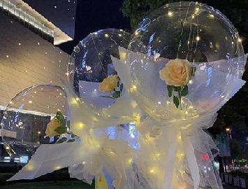 Transparent 3 Bobo Balloon with 3 Yellow rose inside and wrapped in white and pale yellow wrapping and led fairy light string
