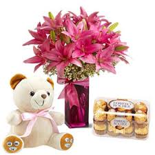A vase of lilies with 16 ferrero chocolates and a teddy bear