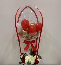 Transparent Balloon stuffed with 3 gold and 3 red balloons Tied with ribbons to a basket of 12 red and white flowers