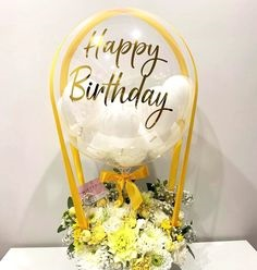 Transparent Balloon Printed Happy Birthday in gold stuffed with 4 white balloons Tied with ribbons to a basket of 12 yellow and white flowers