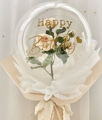 A bouquet of single clear balloon with happy birthday printed wrapped in white and jute white rose inside of balloon