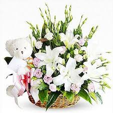 A basket of lilies with teddy bear