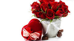 12 red roses in a vase with heart cushion