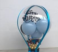 1 bubble balloon with happy birthday print and blue balloons inside with chocolates basket