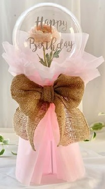 Bouquet of clear printed happy birthday transparent balloon with pink rose in the balloon wrapped in pink and jute bow